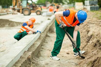 Horizontal image of two builders working hard